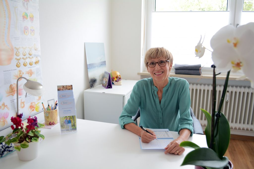 Osteopathin Melita Vajda-Segedi sitzt an ihrem Arbeitsplatz um Kunden entgegenzunehmen